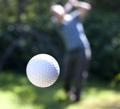 A golf ball in flight — Stock Photo