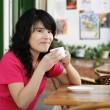 Pretty Asian woman enjoying a coffee — Stock Photo