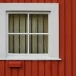 Square window set in a red wooden wall — Stock Photo #3051151