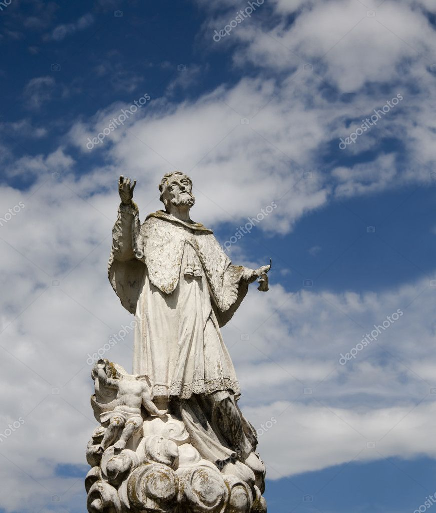 Stone saint statue with headless angel against the blue sky with clouds. — Stock Photo #3319549