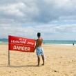 Young boy with a red flag in the beach — Stock Photo
