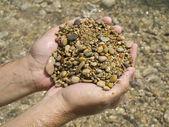 Handen en rivier stenen — Stockfoto