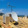 Antenna on a Tile Roof - Stock Photo