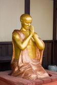 Gold figure of the praying monk — Stock Photo