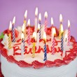 Birthday cake with lit candles - Stock Photo