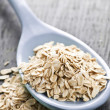 Spoon of uncooked rolled oats - Stock Photo