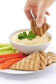 Hand dipping pita in hummus — Stock Photo