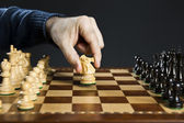 Hand moving knight on chess board — Stock Photo