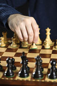 Hand moving pawn on chess board — Stock Photo