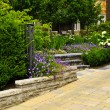 Foto Stock: Landscaped garden and stone paved driveway