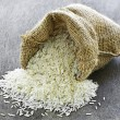 Long grain rice in burlap sack — Stock fotografie