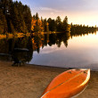 Lake sunset with canoe on beach — Stock Photo #4483033