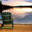 Stock Photo: Wooden chair at sunset on beach