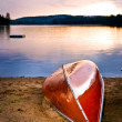 Lake sunset with canoe on beach — Stock Photo