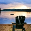 Wooden chair at sunset on beach — Stock Photo