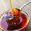 Honey dripping onto spoon — Stock Photo