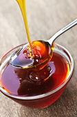 Honey dripping onto spoon — Stock Photo