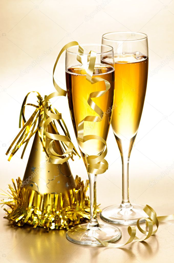 Two full champagne flutes with party hat and ribbons — Stock Photo #4483377