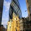 Gherkin building and church of St. Andrew Undershaft in London - Stock Photo