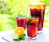Fruit punch in pitcher and glasses — Stock Photo