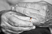 Old hands with wedding band — Stock Photo