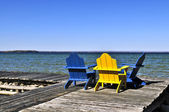 Chairs on wooden dock at lake — Stock Photo
