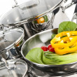 Stainless steel pots and pans with vegetables — Stock Photo