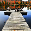Foto Stock: Wooden dock on autumn lake