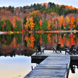 Wooden dock on autumn lake - Stock Photo