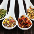 Assorted herbal wellness dry tea in spoons - Stock Photo