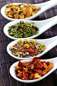 Assorted herbal wellness dry tea in spoons — Stock Photo