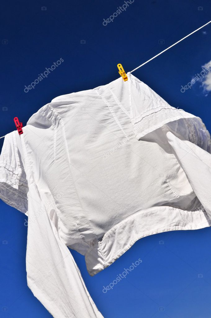 White shirt hanging to dry on clothes line — Stock Photo #4518135