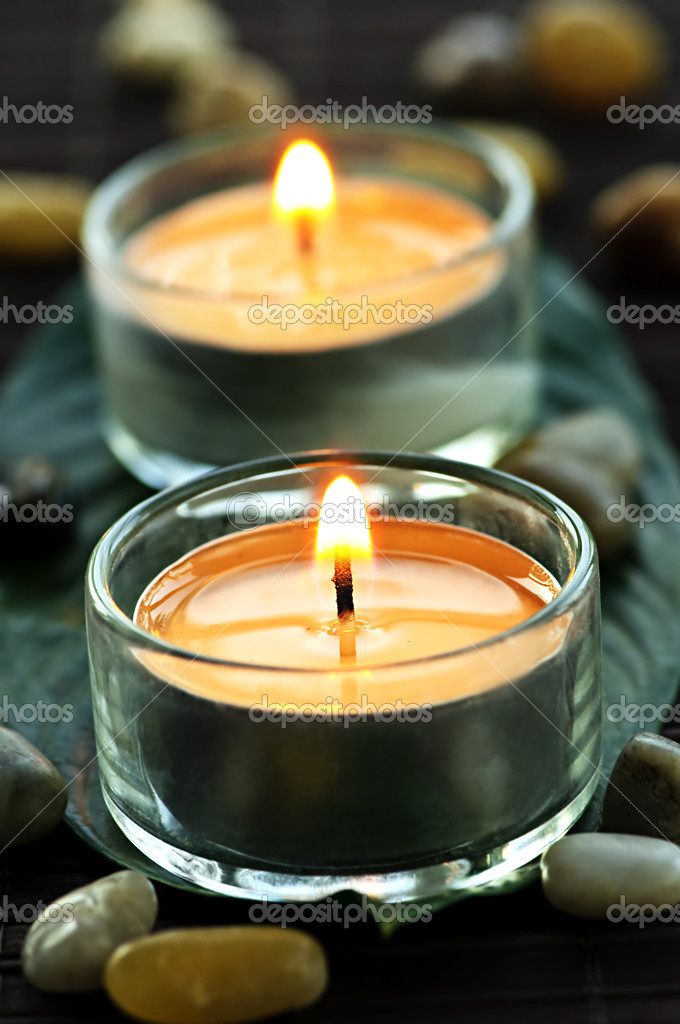 Burning candles in glass holders on green leaf — Stock Photo #4518284