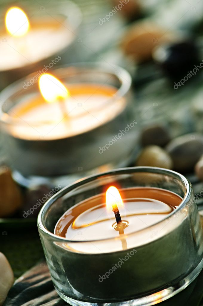 Burning candles in glass holders on green leaf — Stok fotoğraf #4518285