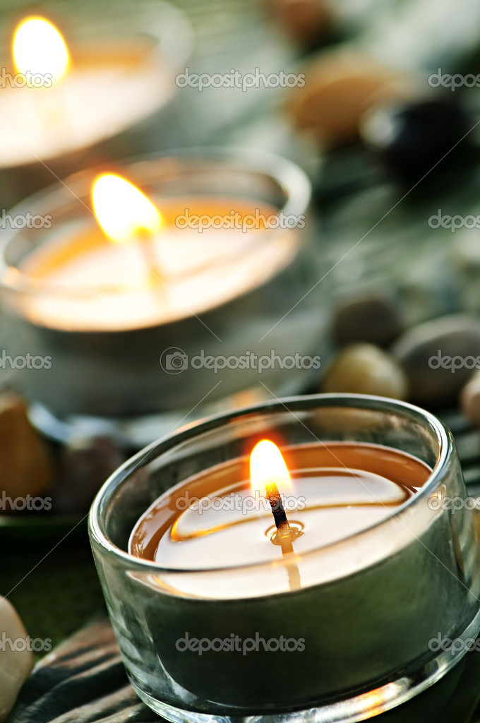 Burning candles in glass holders on green leaf — Lizenzfreies Foto #4518285