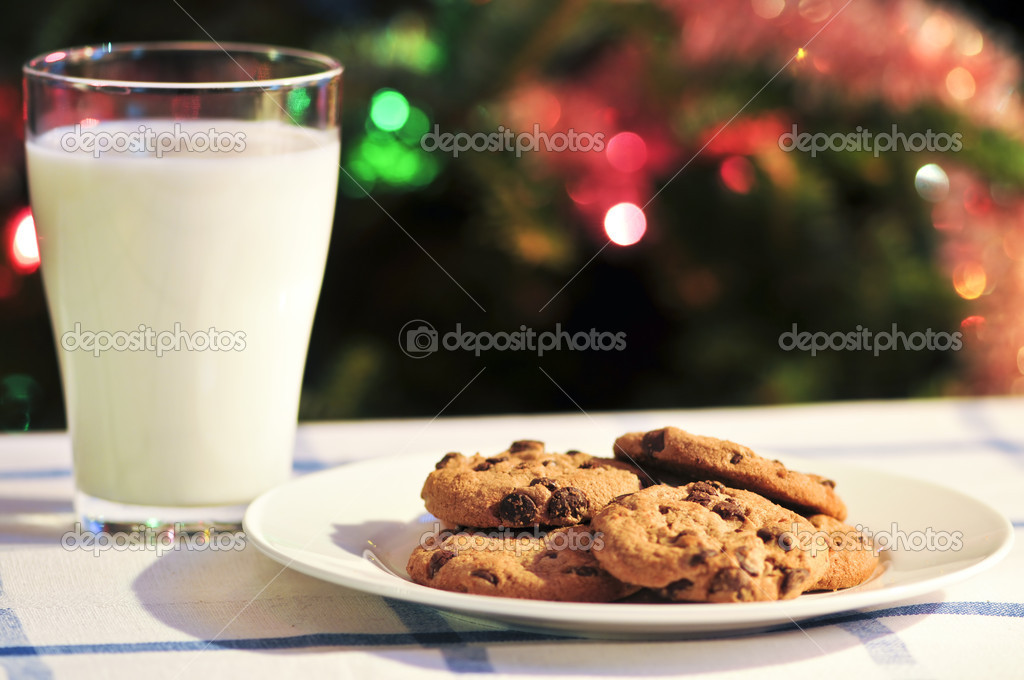 Plate of cookies and glass of milk near Christmas tree — Stock Photo #4518293