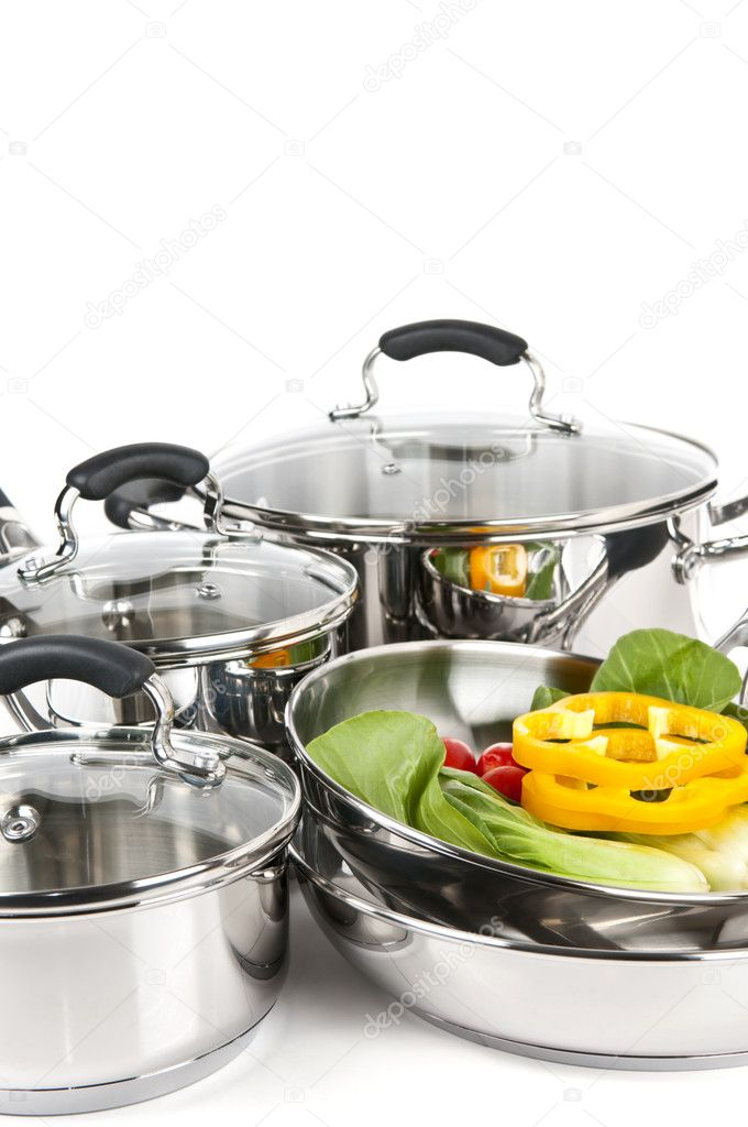 Stainless steel pots and pans isolated on white background with vegetables — Stock Photo #4518496