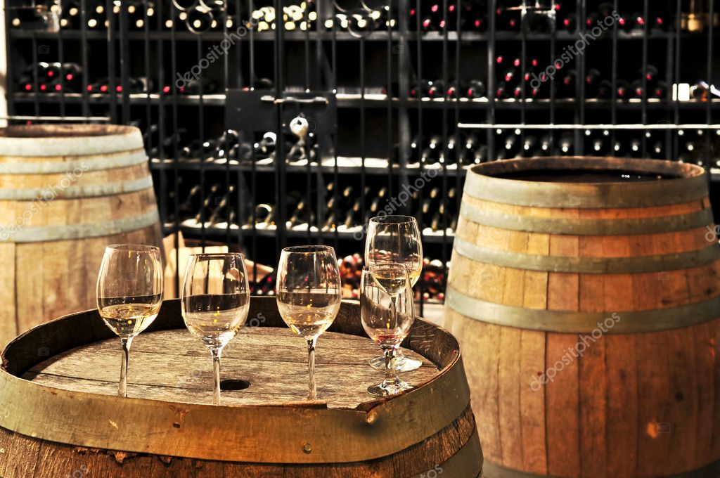 Row of wine glasses on barrel in winery cellar — Stock Photo #4520266