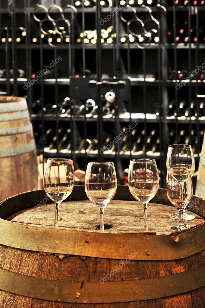 Row of wine glasses on barrel in winery cellar — Stock Photo #4520272