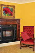 Fireplace and red chair — Stock Photo