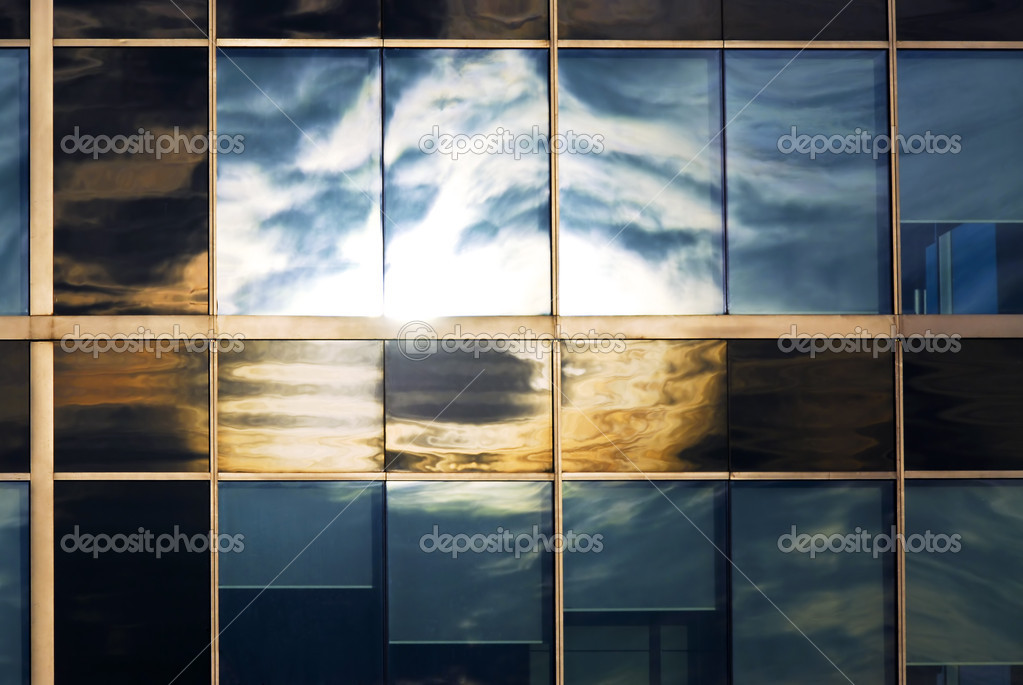 Reflection of a cloudy sky in glass wall of an office building  Stock Photo #4564345