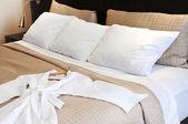 Hotel bed with bathrobe — Stock Photo
