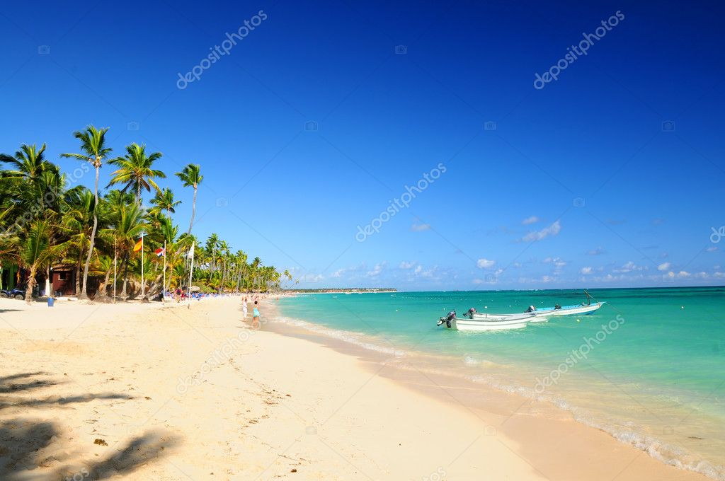 Sandy beach on Caribbean resort and fishing boats at sea — Stock Photo #4635601