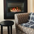 Fireplace and armchair - Stock Photo