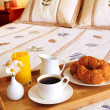 Stock Photo: Breakfast on a bed in a hotel room