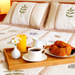Breakfast on a bed in a hotel room - Stock Photo