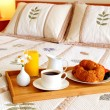 Stock Photo: Breakfast on bed in hotel room