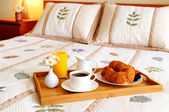 Breakfast on a bed in a hotel room — Stok fotoğraf