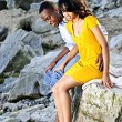 Happy couple sitting at rocky shore — Stock Photo