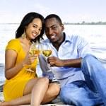 Happy couple having wine on beach — Stock Photo